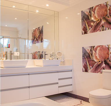 Image showing a modern bathroom with white cabinets and sinks on top of vanity with a flower design on the wall
