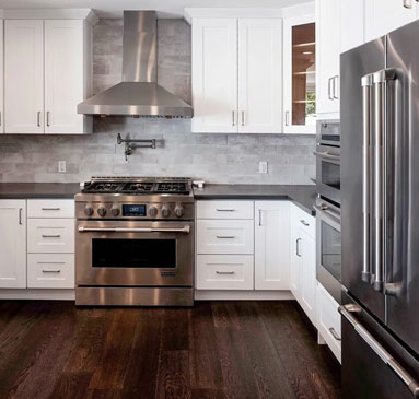 image showing white cabinets with stainless steel appliances and dark wood laminate floor
