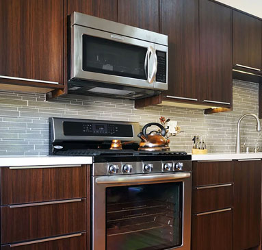 image showing dark wood cabinets and stainless steel appliances